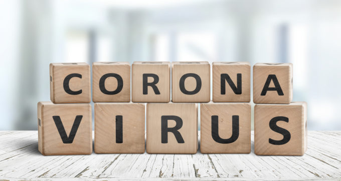 Corona virus alert message on a worn wooden desk | Nursing Home Advice