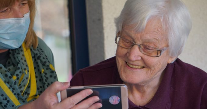 Carer and resident looking at mobile phone | Nursing Home News