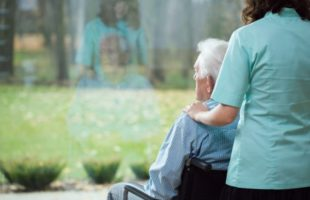 Man in wheelchair at windown with carer standing behind him | Residential Care Management