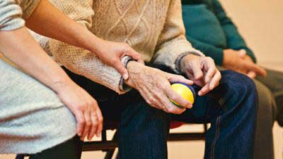 Person holding a ball sitting down | Professional Care Home Advice