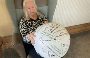 resident living with dementia holding a conversation ball