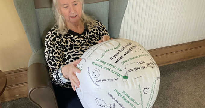 resident living with dementia holding a conversation ball | Care Home Management