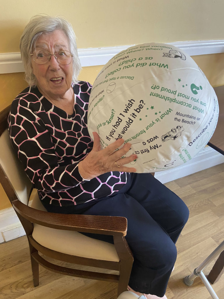 Sadie who is living with dementia holding a conversation ball