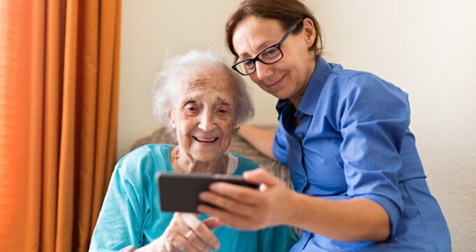 Elderly resident with her care giver looking at a mobile phone | Care Home Providers Guidance