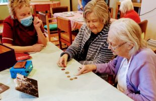 Belmont House Residents looking at pre decimal money | Care Home Supplier News