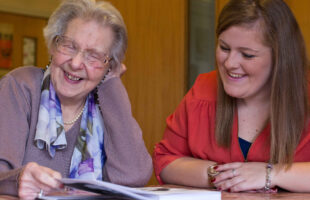Elderly lady and younger lady laughing together | Care Home Supplier News