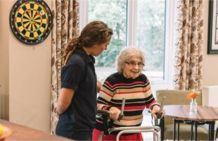 care home resident using walker with care assistant | Care Home Information