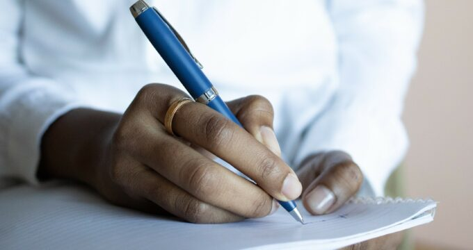 Person writing on notepad | Professional Care Home Advice
