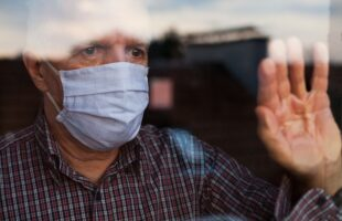 Elderly man at window wearing a facemask | Nursing Home Information