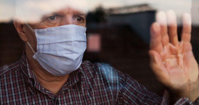 Elderly man at window wearing a facemask | Nursing Home Information