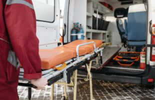 Empty bed trolley being loaded into ambulance | Care Home Providers Guidance