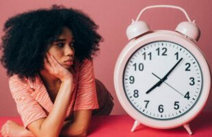 lady beside giant clock | Care Home Professional Magazine
