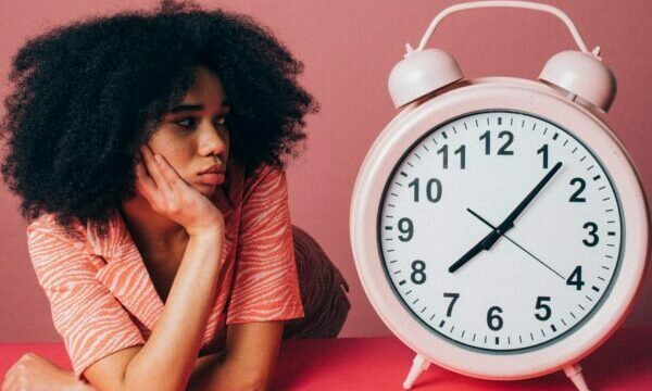 lady beside giant clock   Care Home Professional Magazine