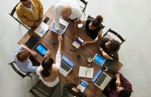 group meeting at a table with laptops, phones, tablets | Residential Care Management